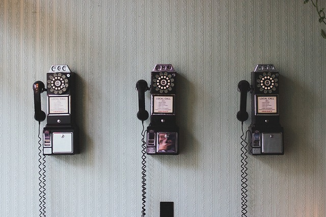 Three rotary dial phones on a gray wall.