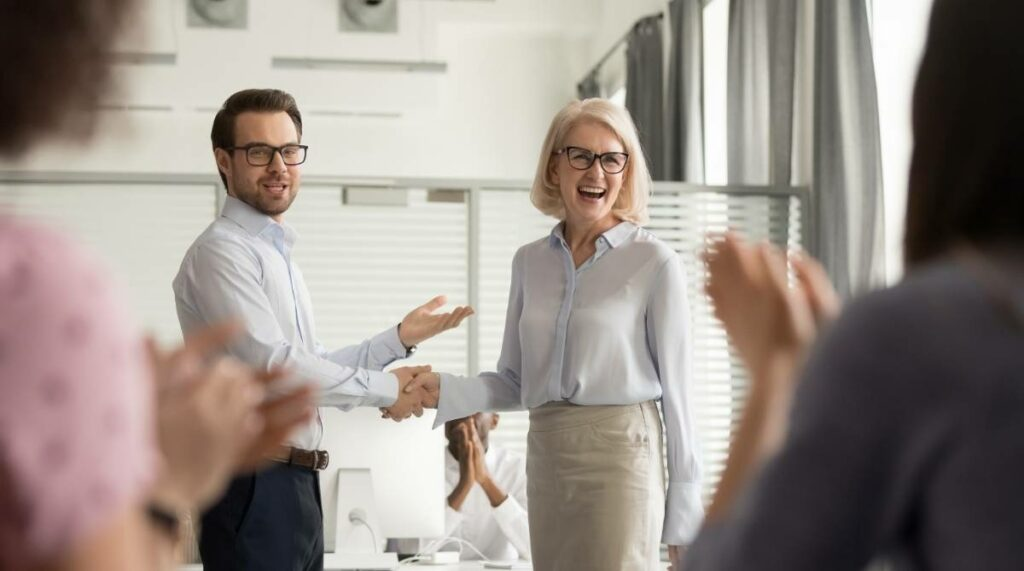 Boss congratulating older worker in front of colleagues
