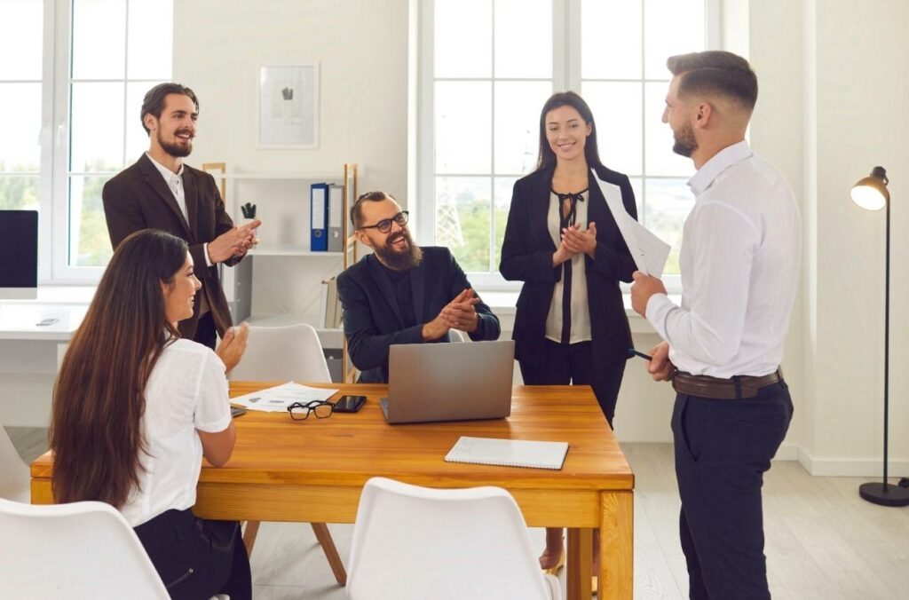 Boss praising employee for a job well done in front of other people by clapping for him.