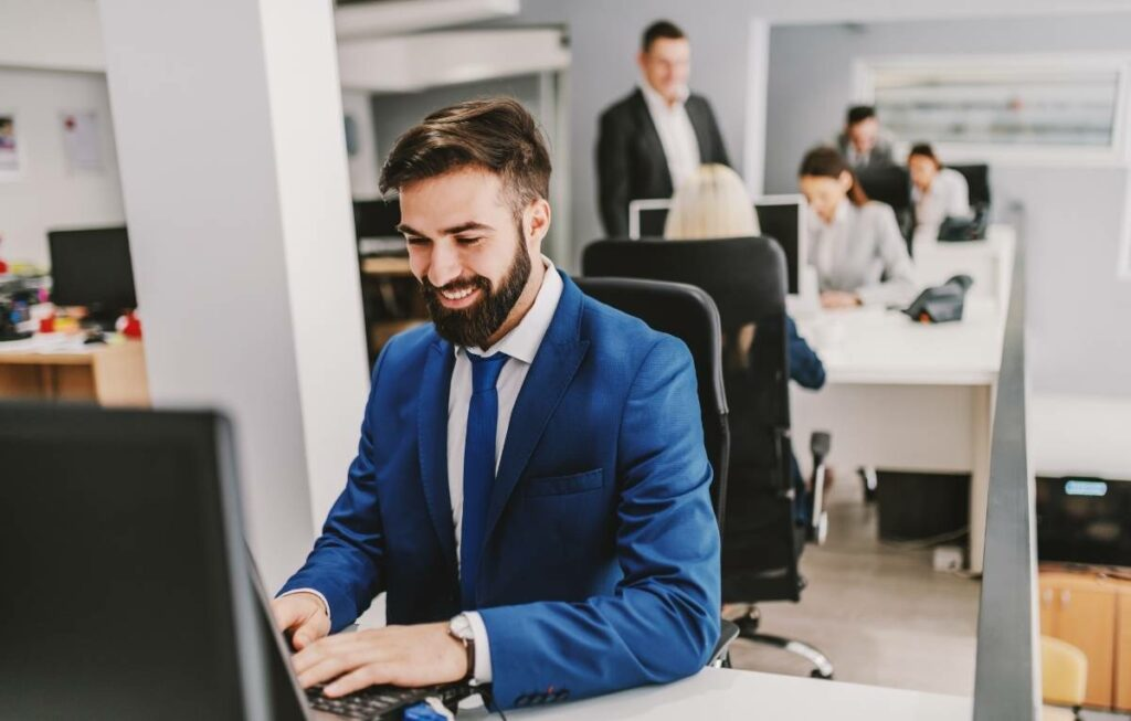 Employee smiling while he works because his boss just told him well done.