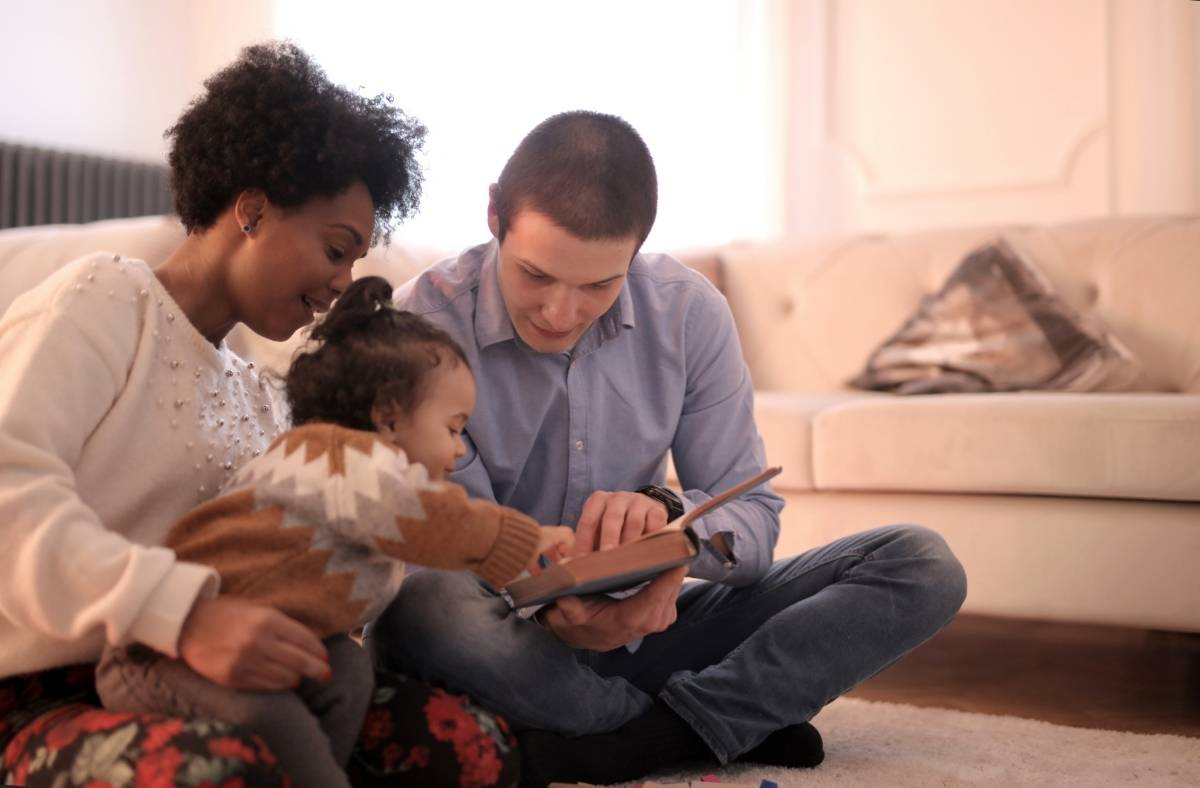 Biracial couple sitting on the floor of their living room reading a book with their small daughter