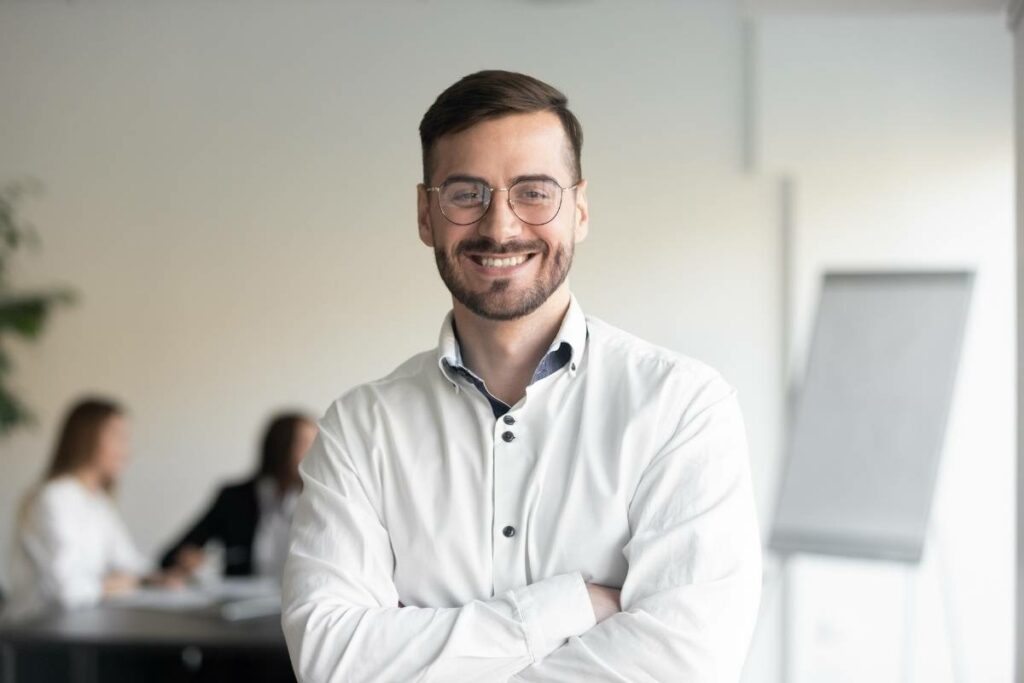 Man With Glasses Smiling Because Executive Coaching Helped Him