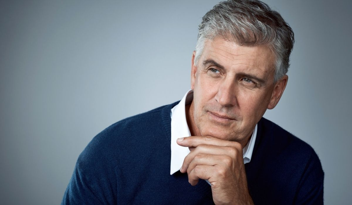 Mature Businessman With Chin on Hand Pondering Self-Awareness in Business