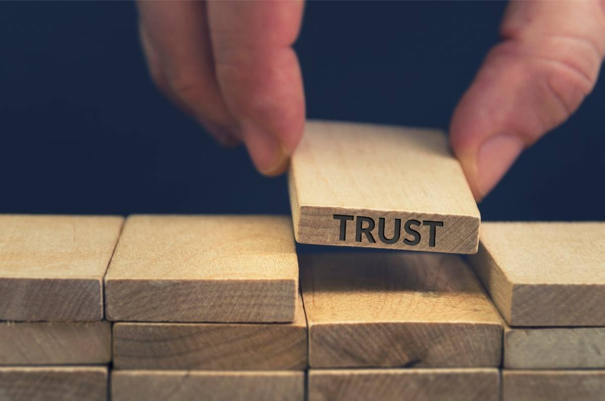 """A Hand Placing Block That Says """"Trust"""" in a wood block wall. """"Building Trust At Work"""""""
