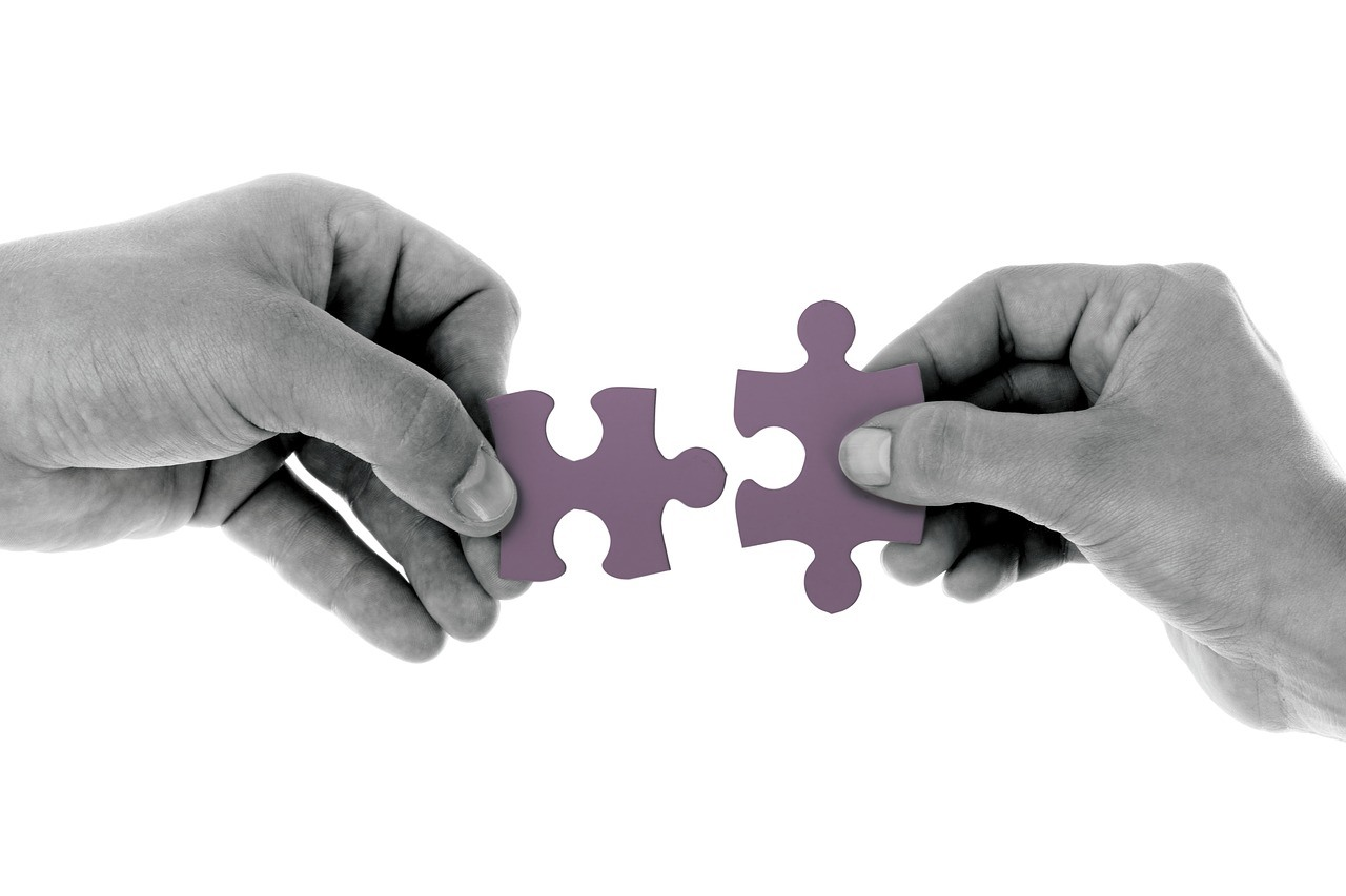 Two hands putting puzzle pieces together to illustrate the importance of connections in business